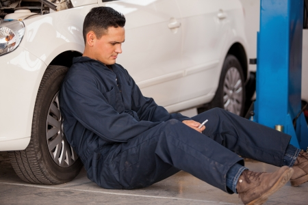 taking a break: Young mechanic taking a break and social networking at an auto shop