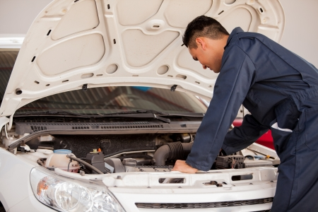 Young man in overall working on a car engine at an auto shop