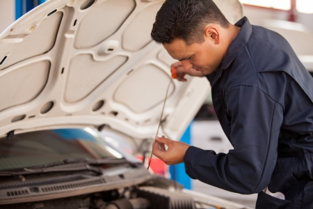 mend: Handsome Latin mechanic measuring the oil level of an engine at an auto shop