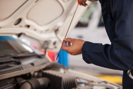 Close-up van een monteur controleren van het oliepeil van een auto bij een auto-shop