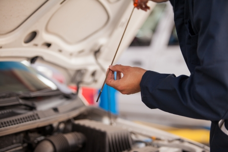 job engine: Closeup of a mechanic checking oil levels of a car at an auto shop