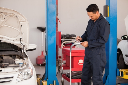 Young Latin mechanic using a checklist for a car inspection at an auto shop