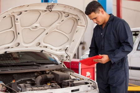 Handsome mechanic using a tablet computer for work in an auto shop Stock Photo