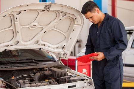 garage automobile: Mécanicien beau à l'aide d'un ordinateur tablette au travail dans un atelier de réparation automobile
