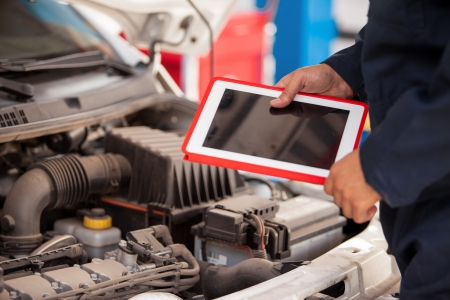 Closeup of a mechanic using a tablet computer next to an open hood in an auto shop photo