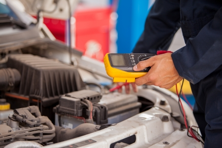 automobile repair shop: Closeup of a mechanic checking a car battery at an auto shop Stock Photo