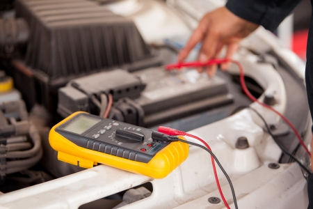Closeup of the hands of a mechanic checking a car battery at an auto shop photo
