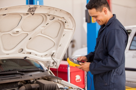Young Latin mechanic using a multimeter to check a battery at an auto shop photo