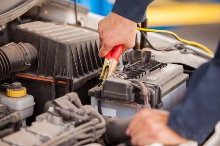 Close-up van de handen van een monteur met behulp van startkabels om een auto te starten Stockfoto