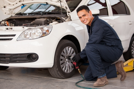 Handsome young man using an air gun to change a tire at an auto shop photo