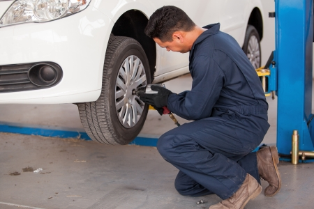 auto shop: Hispanic young mechanic using an air gun to tighten the bolts of a tire from a suspended car Stock Photo