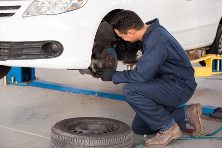 Young mechanic fixing the brakes of a car at an auto shop photo