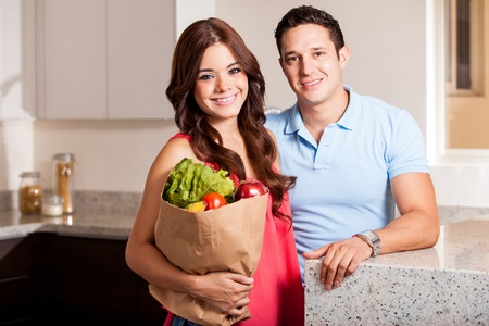 Beautiful young woman and her partner carrying a bag of groceries in the kitchen photo
