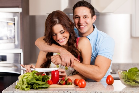 Gorgeous young woman making a salad with her date for dinner photo