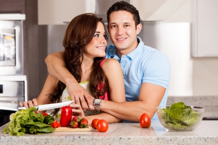 Pretty brunette and her handsome date staying home and cooking dinner together photo