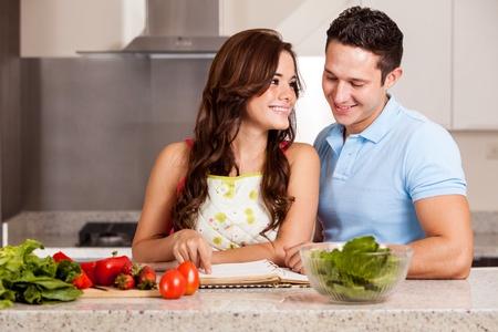 jovenes enamorados: Pareja hispana joven cocina la cena juntos y mirando un libro de cocina para una nueva receta