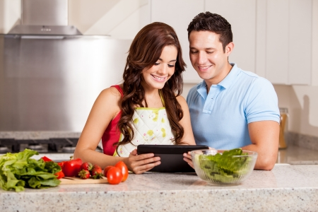 Gorgeous housewife and her husband using a table computer in the kitchen and smiling photo