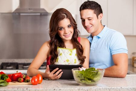 Beautiful young woman and her husband looking for some new recipes and ingredients on a tablet computer photo
