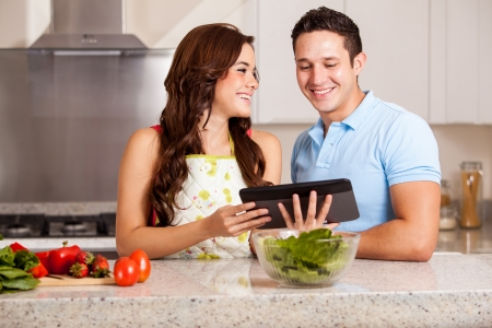 Happy couple looking for a dinner recipe online using a tablet computer photo