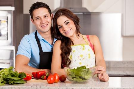 mandil: Pareja joven atractiva, que llevaba delantal y cocinar la cena juntos Foto de archivo