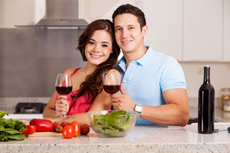 Cute Hispanic couple cooking dinner together and drinking a glass of wine photo
