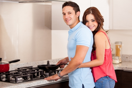 Handsome young man cooking dinner with her girlfriend and smiling photo