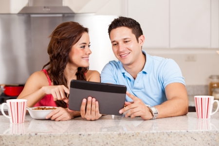 Hispanic couple reading the news on a tablet computer while eating some cereal for breakfast photo