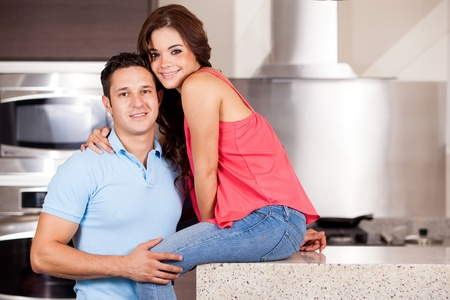 Portrait of a good looking Hispanic couple hanging out in the kitchen photo