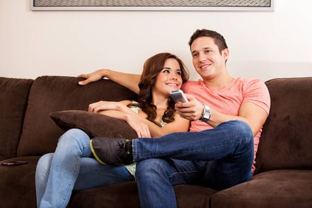 couple on couch: Cute brunette and her boyfriend relaxing on the couch and watching some TV Stock Photo