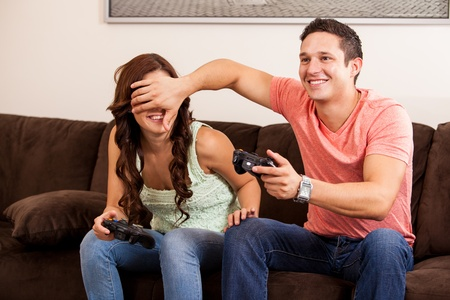Handsome young man cheating on a video game while playing with his girlfriend photo