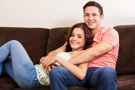 couple on couch: Handsome young Latin man relaxing on a couch and spending time with his girlfriend Stock Photo