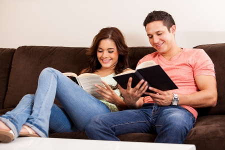 Happy young couple relaxing in the living room and reading a book together photo