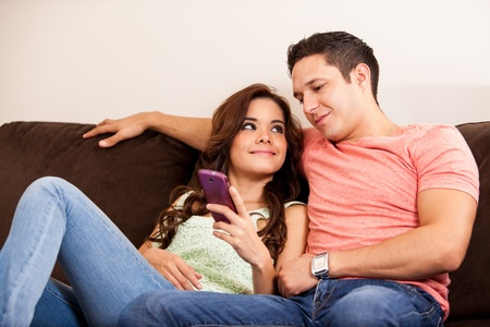 Young Hispanic couple looking at a cell phone while relaxing in the living room photo