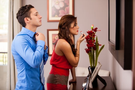woman mirror: Young Hispanic couple getting ready to go out in front of the mirror Stock Photo