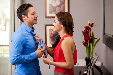 vistiendose: Brunette feliz ayudando a su novio con su corbata antes de ir a una cita Foto de archivo