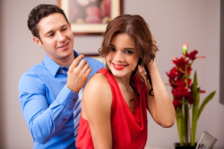 getting together: Beautiful brunette getting some help from her boyfriend to put on a necklace before going out