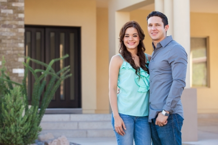 Happy young Latin couple in front of their new house photo