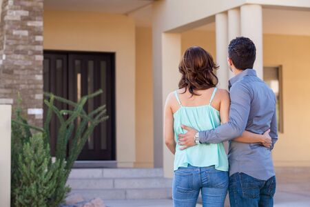real estate house: Cute young couple holding each other and looking at their new house