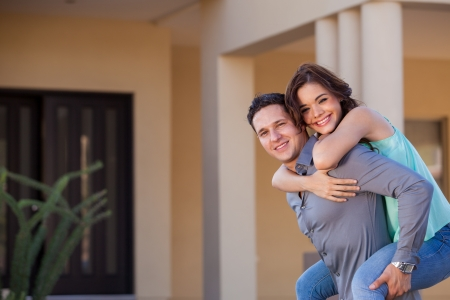 Young woman piggyback riding her husband in front of their new home and smiling