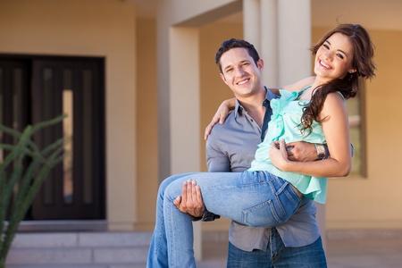 Gelukkige jonggehuwden aankomen om hun nieuwe huis en glimlachend
