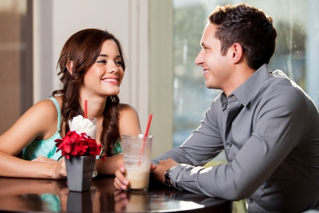 woman in cafe: Cute Latin woman falling in love with a guy on a date at a restaurant Stock Photo