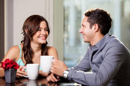 Happy brunette and her attractive date having fun and drinking coffee at a restaurant photo