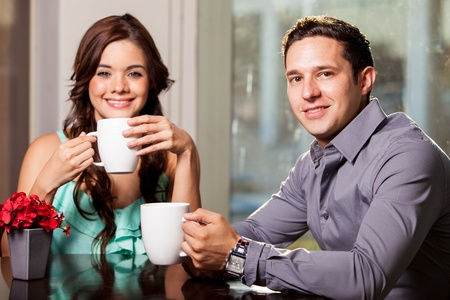 Young Hispanic couple drinking coffee at a restaurant and smiling photo