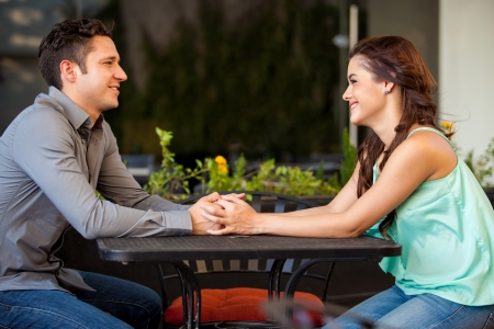 across: Attractive Latin couple holding hands across a table and looking at each other Stock Photo