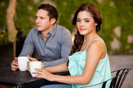 Cute young brunette drinking coffee on a first date photo