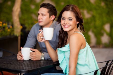 Beautiful young woman drinking some coffee with her boyfriend at a coffee shop photo