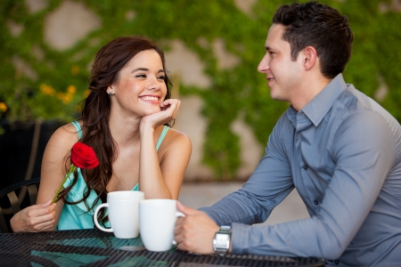 got: Beautiful girl just got a red rose from her boyfriend on a date at a cafe