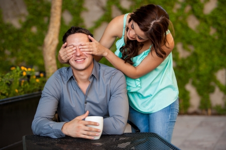Pretty brunette surprising her date by covering his eyes from behind photo