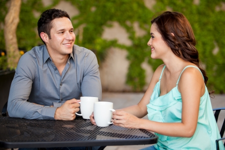 first date: Good looking Latin couple drinking coffee and smiling on their first date at a restaurant Stock Photo