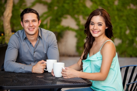 Attractive Latin couple having some coffee together at a terrace photo
